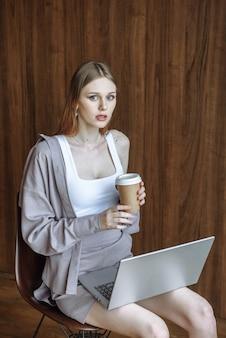 Porträt der jungen schönen frau mit dem kaffee, der mit laptop sitzt