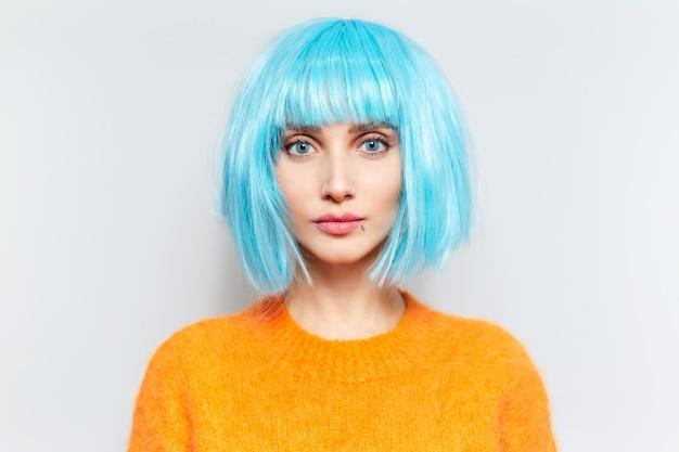 Porträt der jungen schönen frau mit den blauen augen und dem bob-haarschnitt, den orangefarbenen pullover tragend.