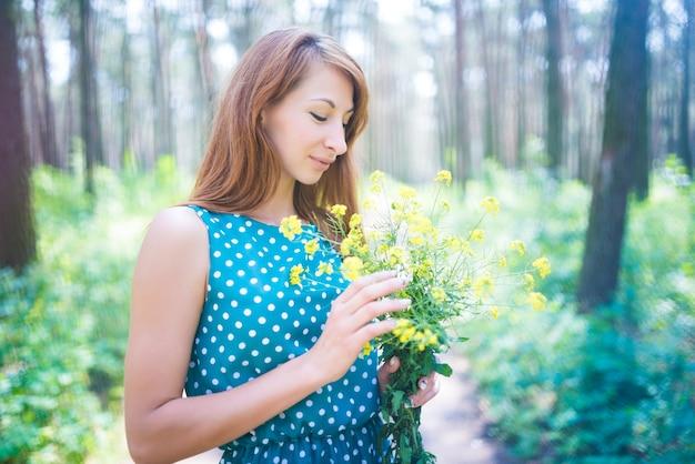 Porträt der jungen schönen frau mit den grünen augen, die gelbe blumen über grünem unscharfem hintergrund halten