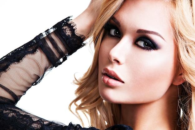 Porträt der jungen schönen frau mit dunklem make-up der augen. modemodell über weißem hintergrund.