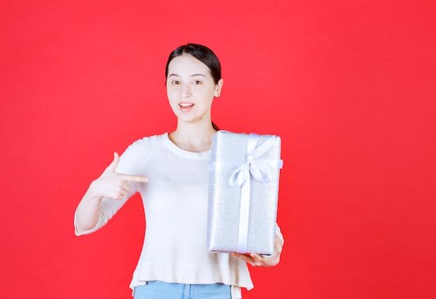 Porträt der jungen schönen frau mit geschenkbox und zeigefinger darauf