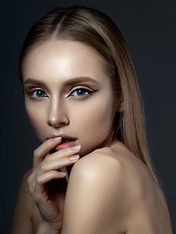 Porträt der jungen schönen frau mit goldenen lidschatten und asymmetrischen eyeliner-flügeln der modernen mode.