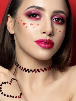 Porträt der jungen schönen frau mit mode bilden mit kleinen herzen auf ihrer wange. moderne leuchtend rosa lippen und rauchige augen. valentinstag konzept. speicherplatz kopieren