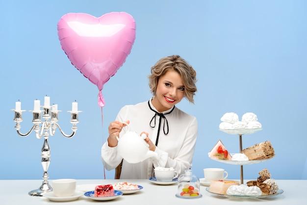 Porträt der jungen schönen frau mit süßigkeiten über der blauen wand