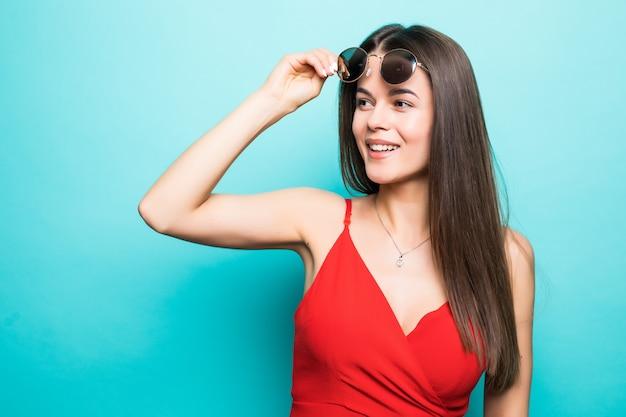Porträt der jungen schönen frau, stilvolles rotes kleid, modetrend, in der sonnenbrille auf der blauen wand