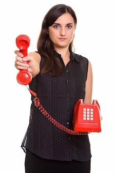 Porträt der jungen schönen frau unter verwendung des alten telefons