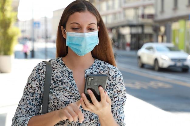Porträt der jungen schönen geschäftsfrau, die chirurgische maske trägt, die auf handy in der stadtstraße tippt