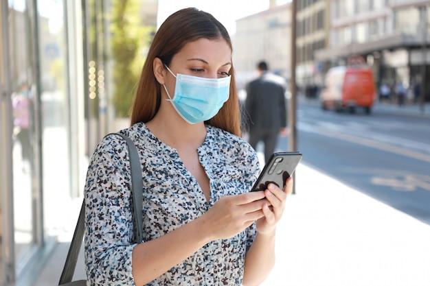 Porträt der jungen schönen geschäftsfrau, die chirurgische maske unter verwendung der smartphone-app in der stadtstraße trägt