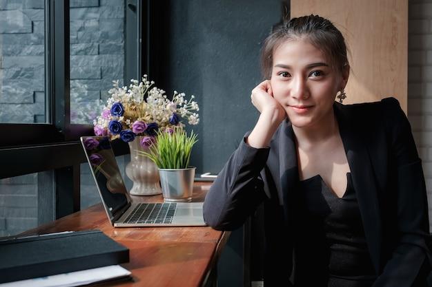 Porträt der jungen schönen geschäftsfrau, die im mitarbeitenden raum sitzt.