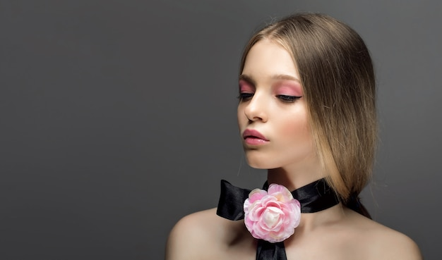 Porträt der jungen schönen gesunden frau mit fantastischem rosarosenzusatz