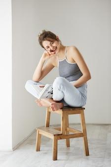 Porträt der jungen schönen glücklichen frau, die lachendes lachendes haltebuch sitzt, das auf stuhl über weißer wand zu hause sitzt.