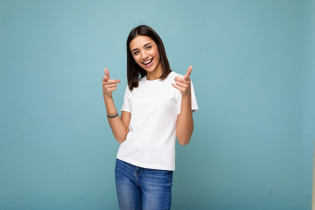 Porträt der jungen schönen glücklichen lächelnden brünetten frau, die modisches weißes t-shirt mit leerem trägt
