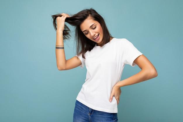 Porträt der jungen schönen glücklichen lächelnden brünetten frau, die trendiges weißes t-shirt mit leerem trägt