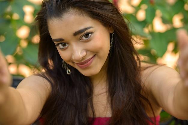 Porträt der jungen schönen indischen frau am park