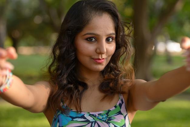 Porträt der jungen schönen indischen frau, die am park draußen entspannt