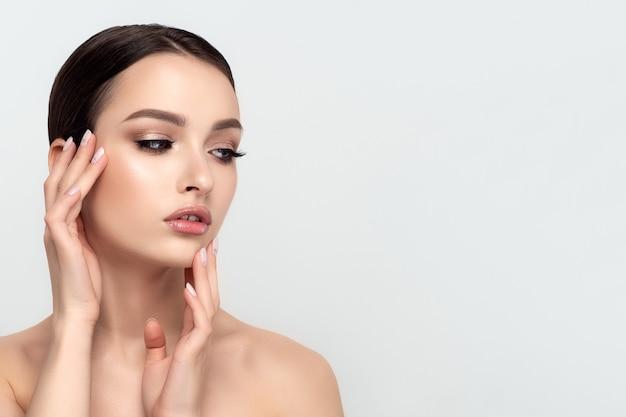 Porträt der jungen schönen kaukasischen frau, die ihr gesicht berührt. reinigungskonzept für haut, hautpflege und kosmetologie