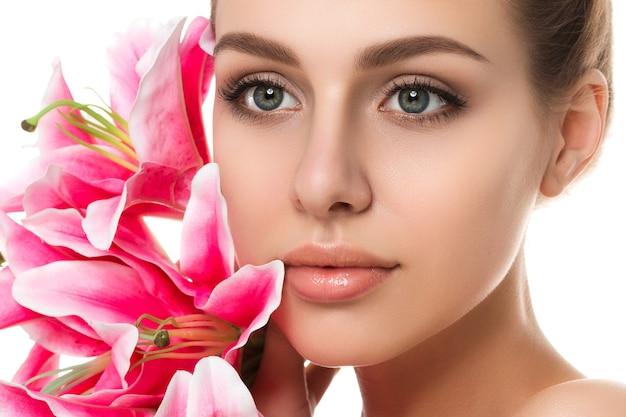 Porträt der jungen schönen kaukasischen frau mit den rosa lilien lokalisiert. reinigungsgesicht, perfekte haut. spa-therapie, hautpflege, kosmetologie