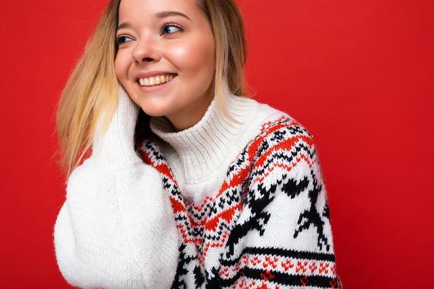 Porträt der jungen schönen lächelnden blonden frau des hippies in der modischen winterstrickjacke sexy sorglos