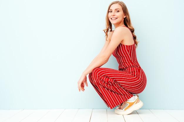 Porträt der jungen schönen lächelnden frau in der modischen roten anzugkleidung des sommers