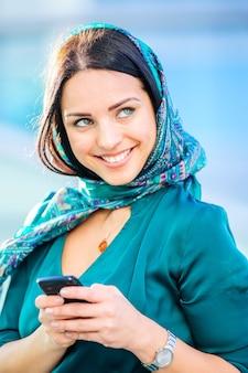 Porträt der jungen schönen lächelnden frau mit schal auf ihrem kopf unter verwendung des smartphones