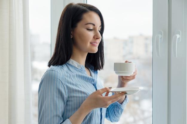 Porträt der jungen schönen lächelnden frau mit tasse kaffee