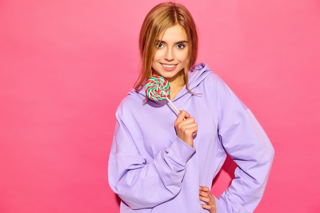 Porträt der jungen schönen lächelnden hippie-frau im modischen sommer hoodie. sexy sorglose frau, die nahe rosa wand aufwirft. positives modell mit lutscher