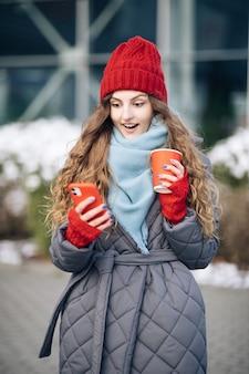 Porträt der jungen schönen lockigen frau in der winterkleidung, die telefon hält, feiern gutes mobiles nachrichtenüberraschungsgebot.