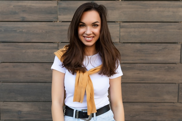 Porträt der jungen schönen positiven glücklichen brünetten frau, die gegen die braune wand auf der straße steht