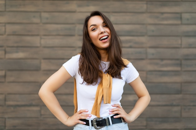 Porträt der jungen schönen positiven glücklichen brunettefrau, die gegen braune wand auf der straße steht und stilvolles outfit trägt.