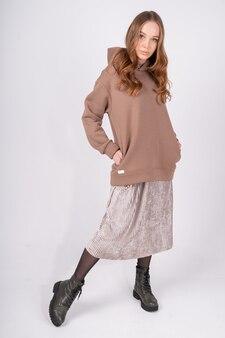 Porträt der jungen schönen rothaarigen frau in den kuscheligen kleidern sexy weibliches modemodell wirft in taupe auf