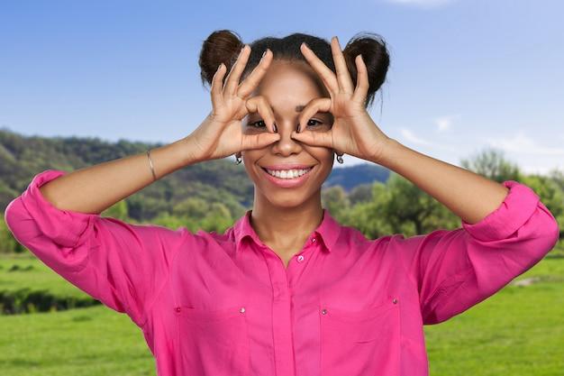 Porträt der jungen schönen schwarzen frau lässt gläser mit den fingerhänden gestikulieren