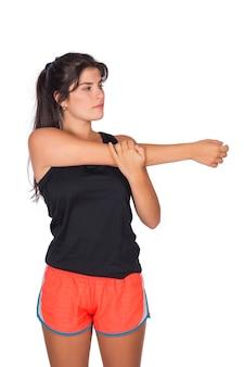 Porträt der jungen schönen sportfrau, die sportkleidung trägt und sich vor übung im studio ausdehnt. sport- und lifestyle-konzept.