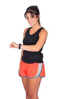 Porträt der jungen schönen sportfrau, die sportkleidung trägt und zeit von der intelligenten uhr im studio prüft.