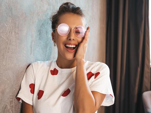 Porträt der jungen schönen überraschten frau mit den händen nahe gesicht modisches mädchen in der zufälligen sommerkleidung entsetzte frau, die nahe grauer wand im innenraum im studio in der sonnenbrille aufwirft
