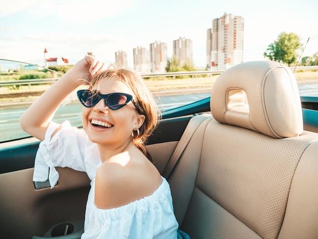 Porträt der jungen schönen und lächelnden hippie-frau im cabrio-auto