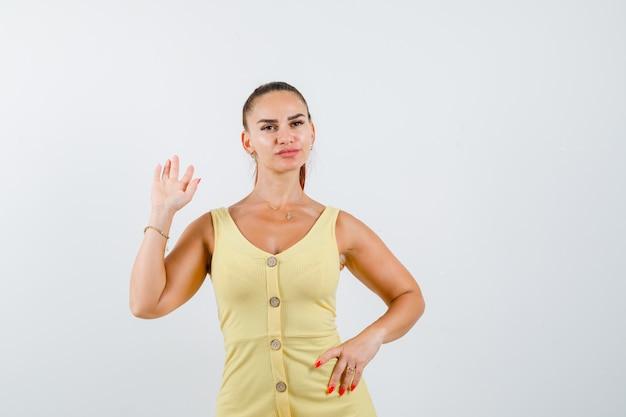 Porträt der jungen schönen weiblichen winkenden hand zum begrüßen, während hand auf hüfte im kleid gehalten wird und selbstbewusste vorderansicht schaut