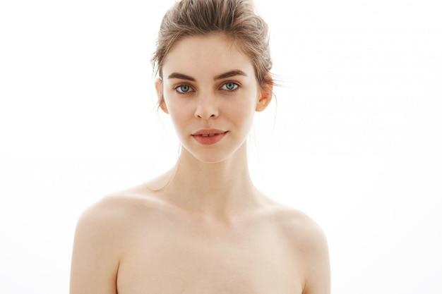Porträt der jungen schönen zarten nackten frau mit brötchen über weißem hintergrund.