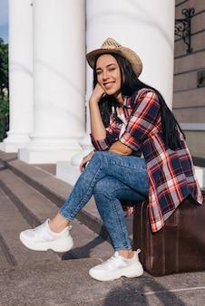 Porträt der jungen schönheit sitzend auf der gepäcktasche, die kamera betrachtet