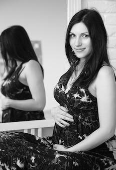 Porträt der jungen schwangeren frau in einem schwarzen kleid.
