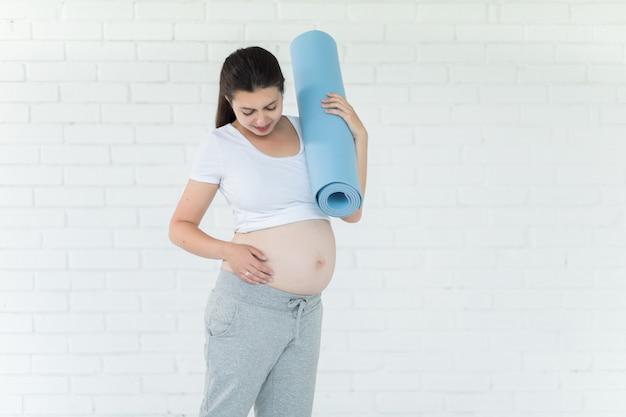 Porträt der jungen schwangeren frau mit yogamatte