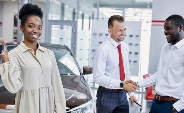 Porträt der jungen schwarzen dame mit schlüsseln des neuen autos in den händen