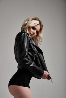 Porträt der jungen sexy blonden frau in stilvollem body und lederjacke und golf