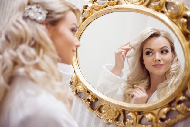 Porträt der jungen sexy frau in einem bademantel, der den spiegel betrachtet.