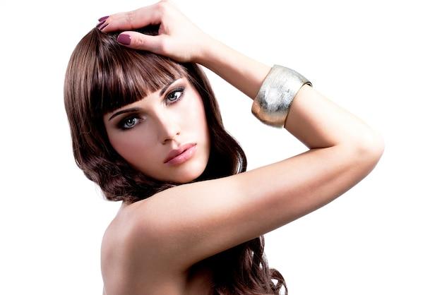 Porträt der jungen sexy frau mit den langen braunen haaren. hübsches mädchenmodell mit stilvoller bijouterie der silbernen farbe.