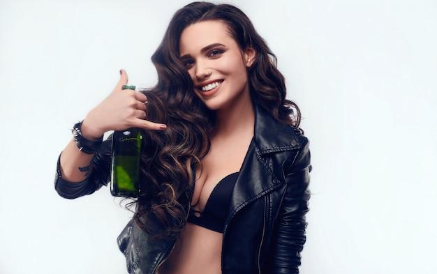 Porträt der jungen sexy frau mit langen haaren in der lederjacke, die flasche bier hält