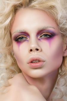 Porträt der jungen sinnlichen frau mit blondem lockigem haar und modeclown-make-up