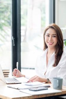 Porträt der jungen smiley-asiatin, die kamera betrachtet und an laptop-computer im modernen büroraum, vertikale ansicht arbeitet.