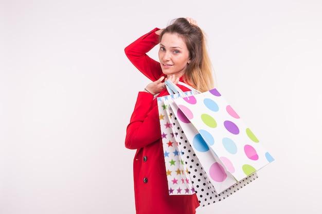 Porträt der jungen sommersprossigen blonden frau mit einkaufstüten auf weißem hintergrund