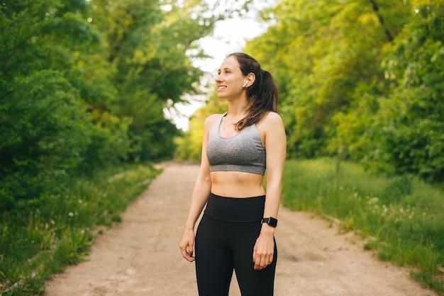Porträt der jungen sportfrau, die sportkleidung im freien im park während des sonnenuntergangs trägt