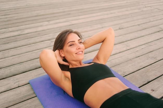Porträt der jungen sportfrau, die übung für bauchmuskeln tut